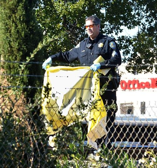 The Associated Press A BART police officer covers one of the two people that were struck and killed by a moving BART train along Jones Road in Walnut Creek, Calif., on Saturday, Oct. 19, 2013. (AP Photo/The Mercury News, Dan Rosenstrauch